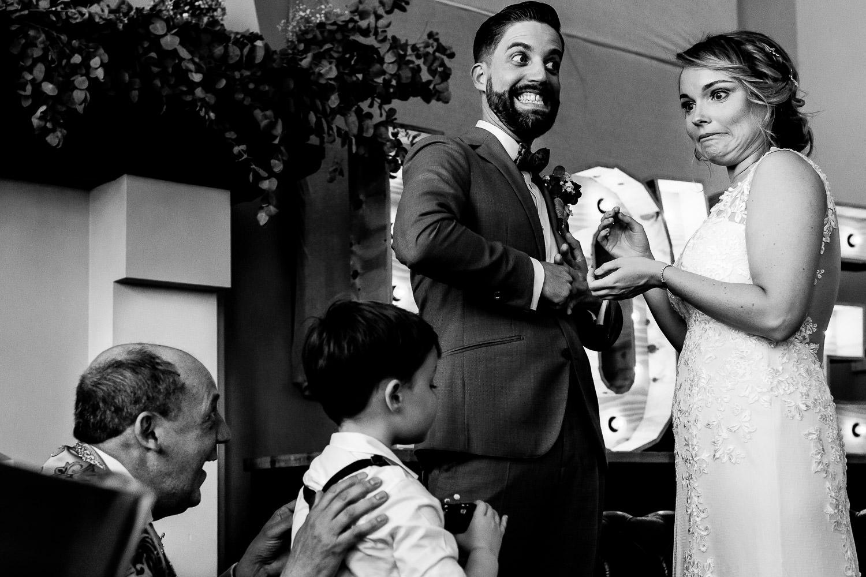Zwart wit foto van een verschrikt kijkende bruid die de ring niet om krijgt bij haar bruidegom