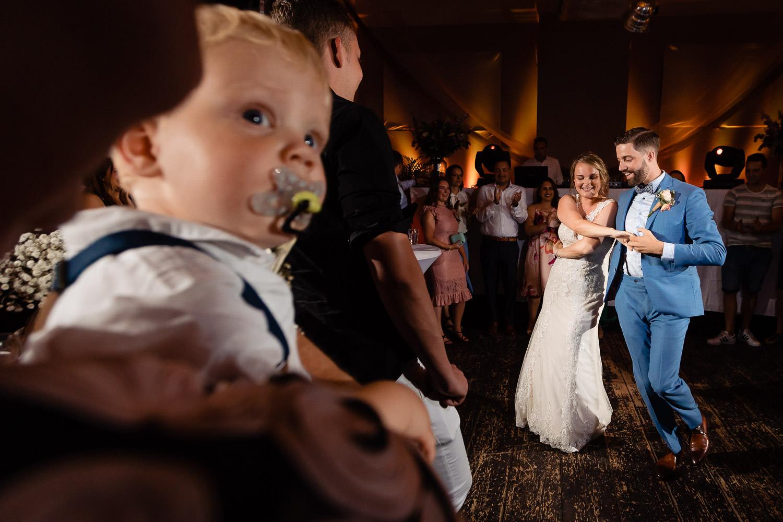 Dansend bruidspaar met een klein jongetje met een speen op de voorgrond