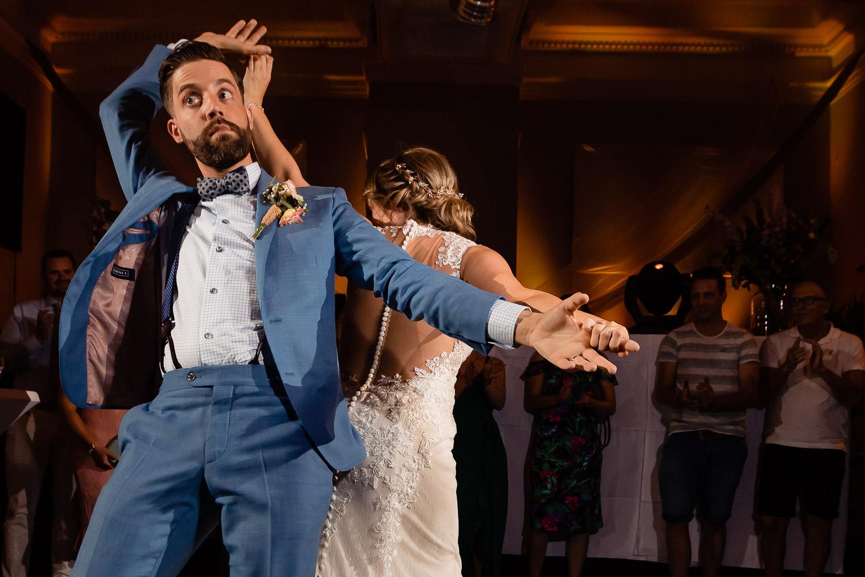 Het bruidspaar doet grappige dansmoves en de gasten klappen