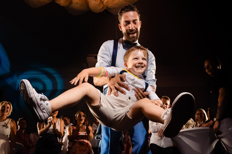 De bruidegom draait vrolijk een klein jongetje al dansend rond