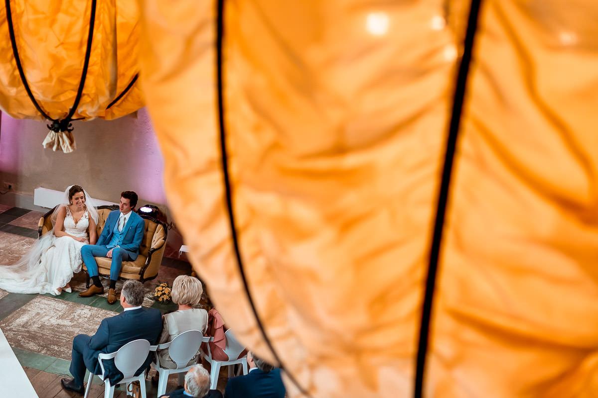 Bruidspaar zit op een bankje tijdens de ceremonie