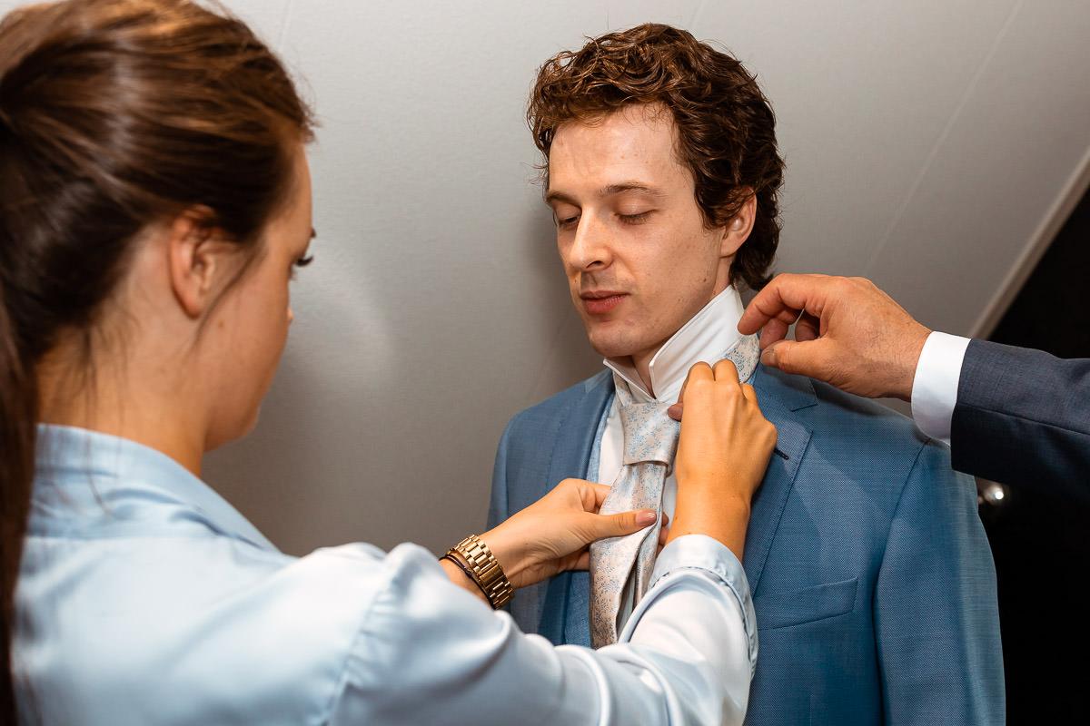 bruidegom wordt geholpen met stropdas