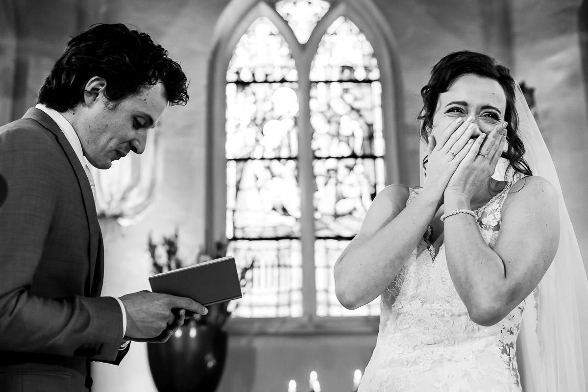 Bruid lacht terwijl bruidegom geloften uitspreekt