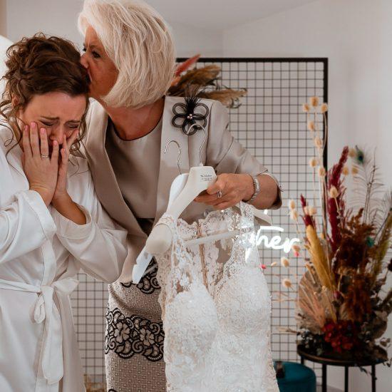 Moeder troost bruid die met volle emoties kijkt naar dr jurk