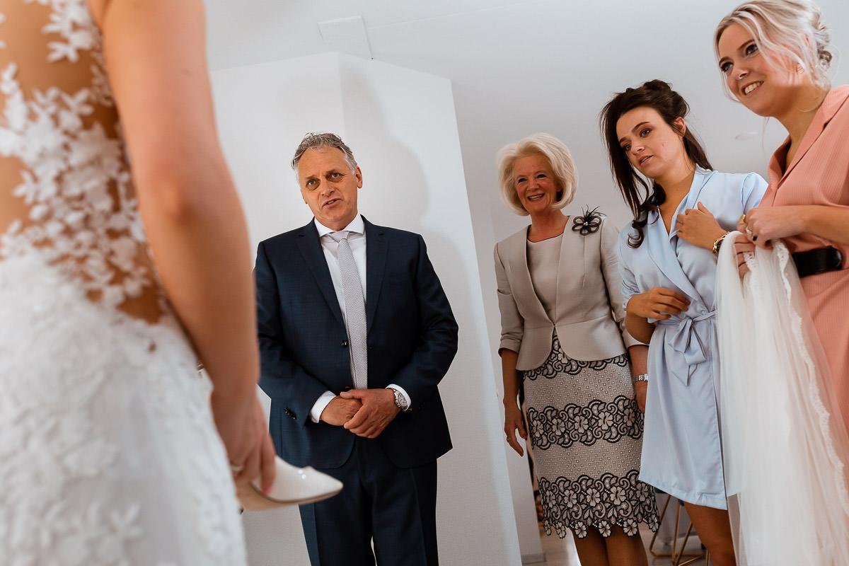Familie kijkt naar de bruid tijdens het aantrekken van de trouwschoenen