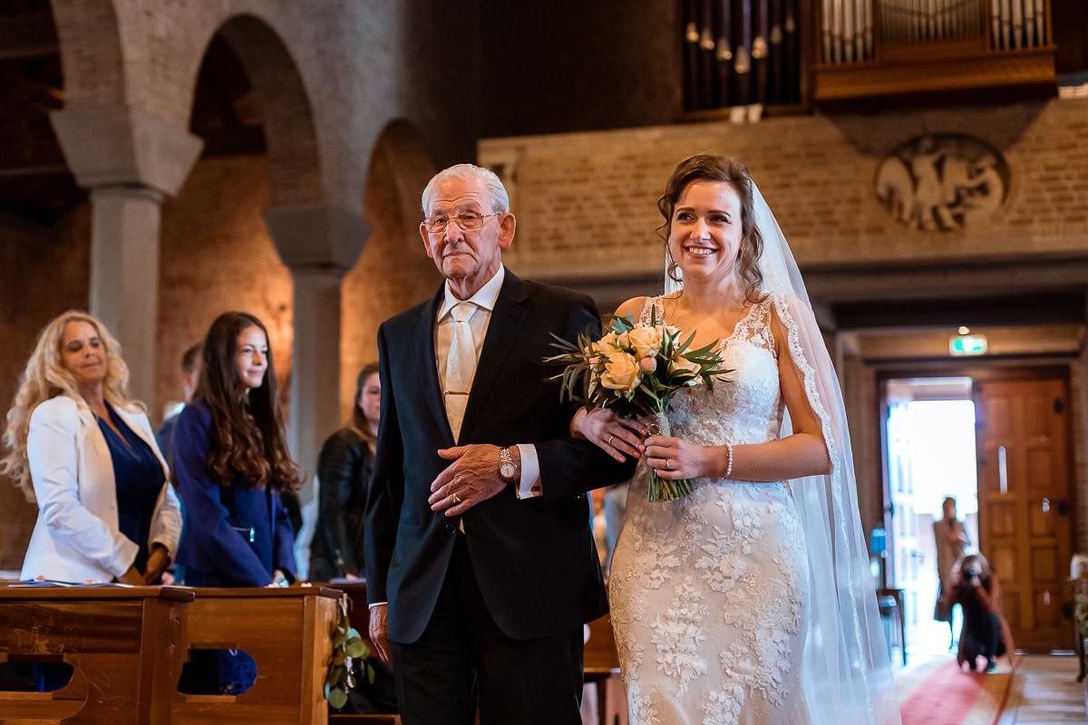 Bruid loopt samen met opa de kerk in