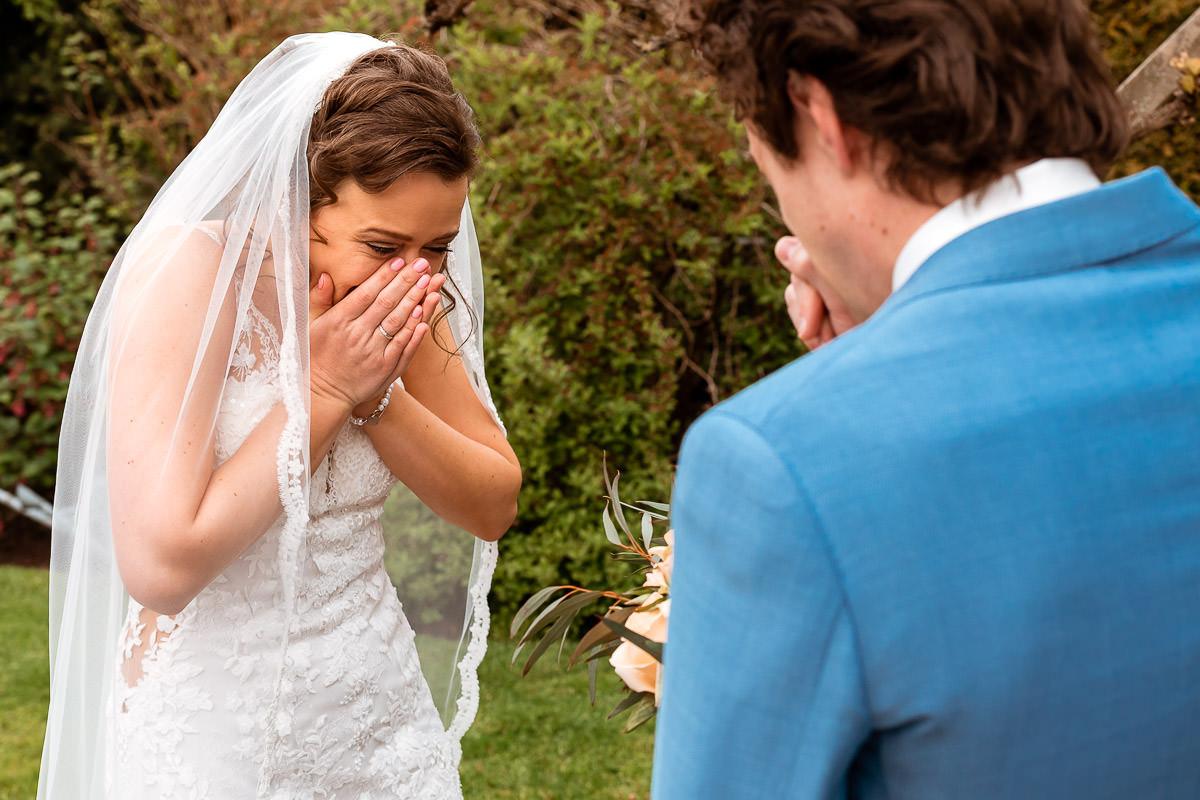 Bruid kijkt verbaast naar bruidegom tijdens de first look