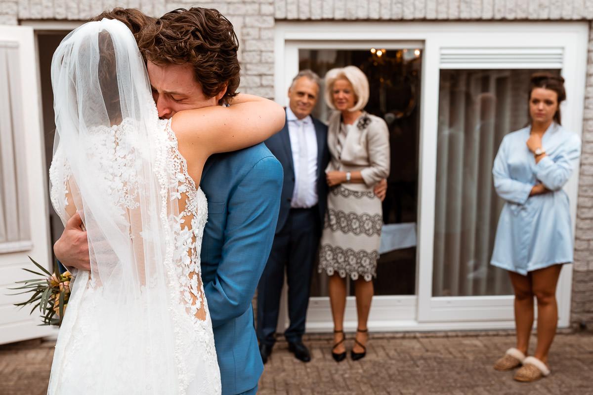 Bruidspaar omhelst elkaar intenst met ouders en zus op de achtergrond