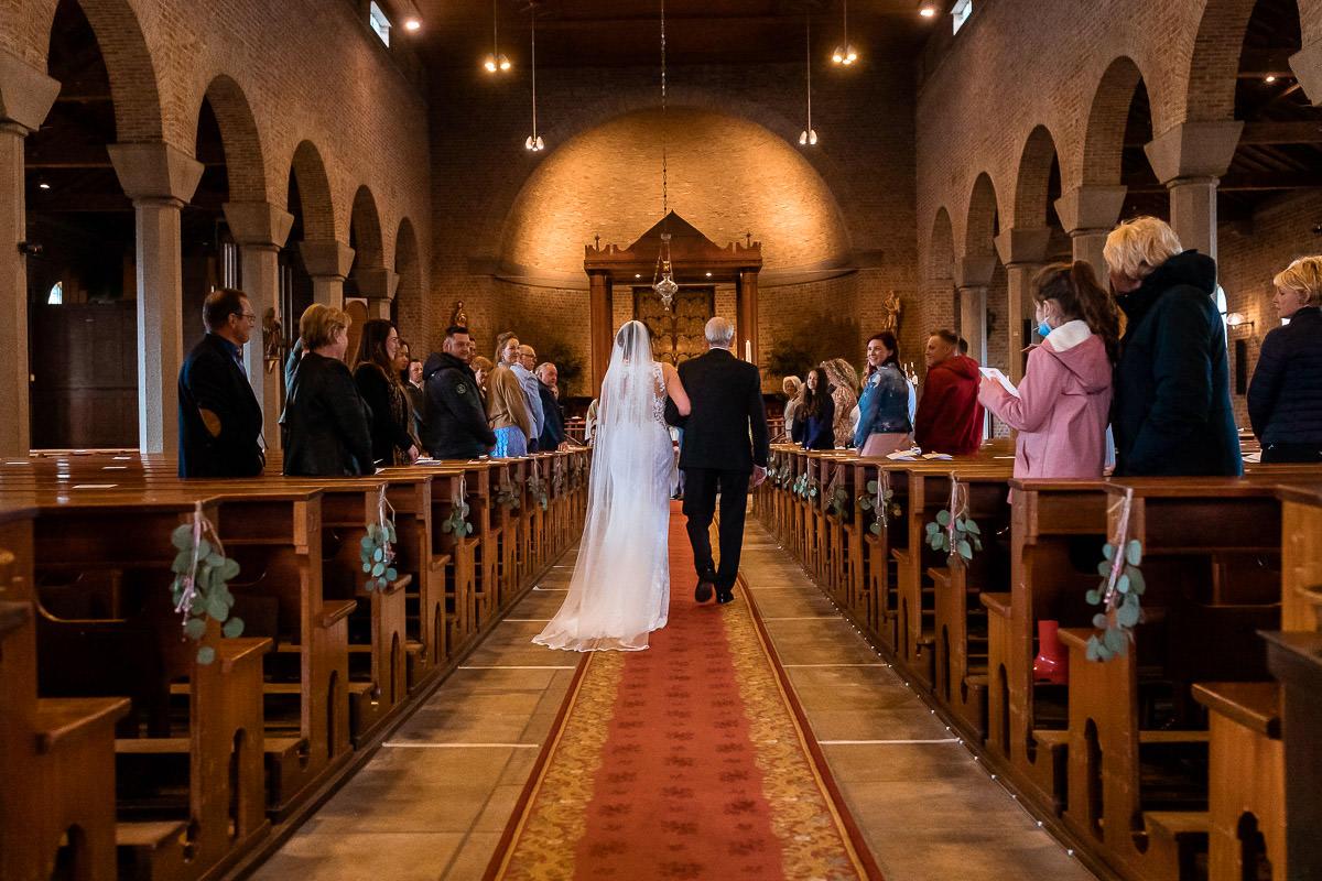 Bruid loopt arm in arm de kerk in met opa