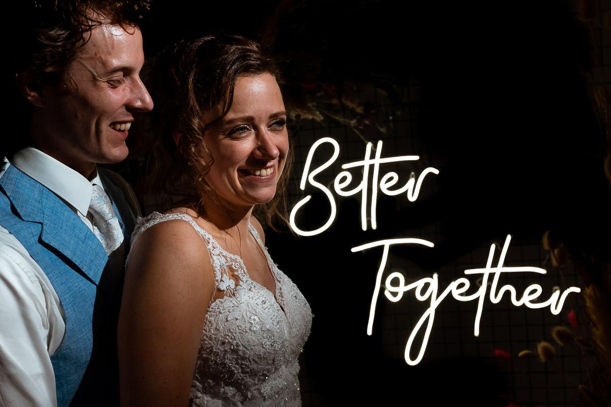 bruidspaar lachend voor lichtgevende letters better together