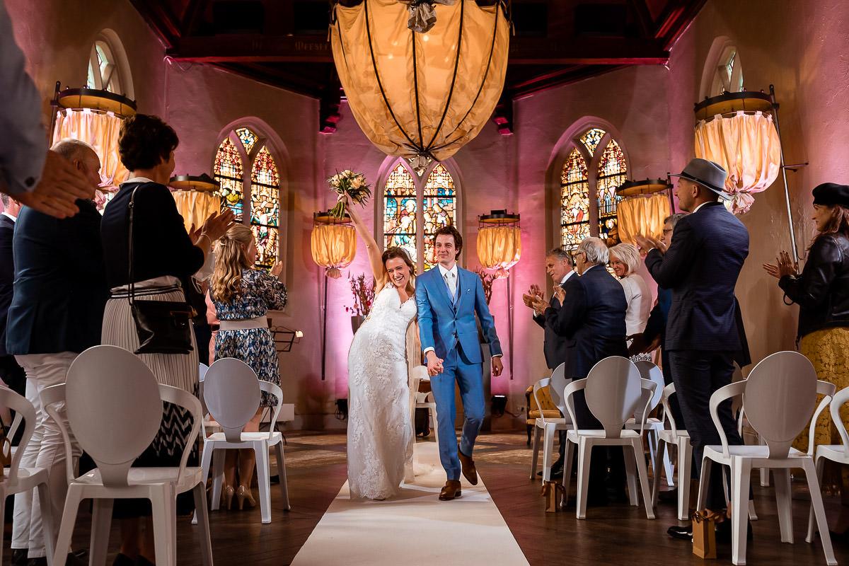 Bruid juicht uitbundig terwijl ze van het altaar aflopen
