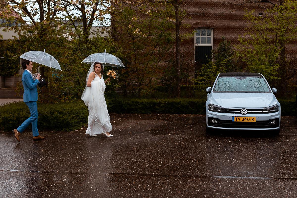Bruidspaar loopt met paraplus naar de auto