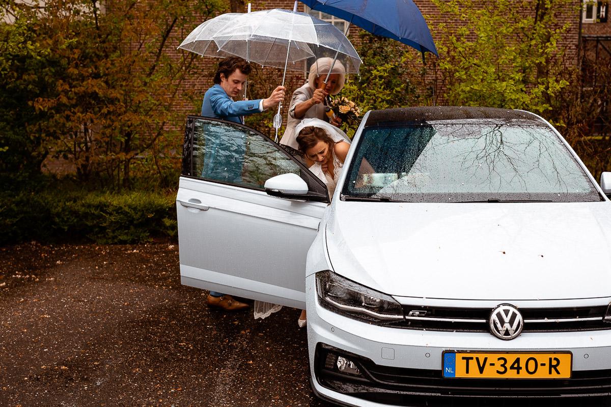 Bruid stapt de auto in met hulp van bruidegom en moeder die paraplus vast houden