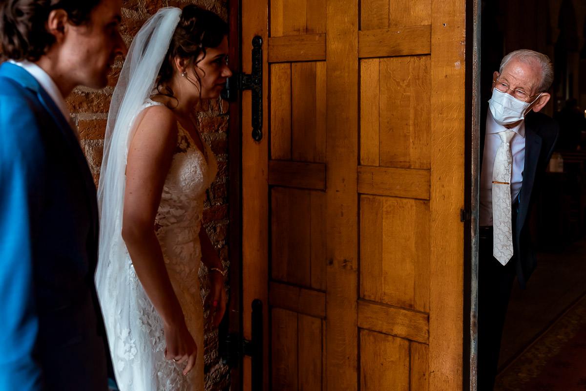 Opa kijkt met mondkapje naar bruidspaar