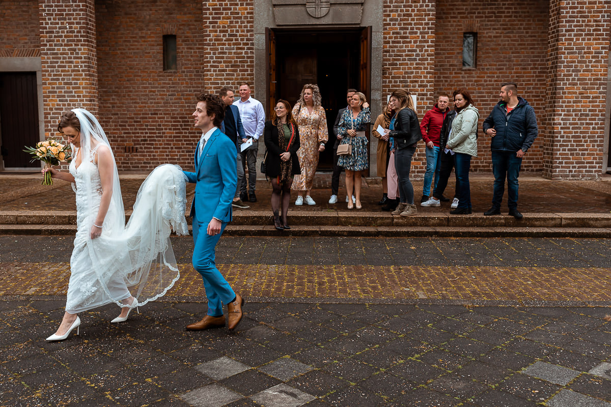 bruidspaar loopt weg van de kerk met gasten op de achtergrond