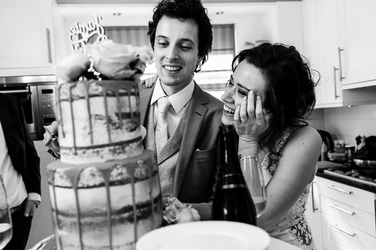 bruid knuffelt bruidegom tijdens taart aansnijden