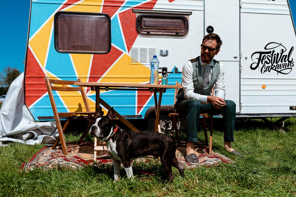 Bruidegom zit voor de caravan samen met zijn hond