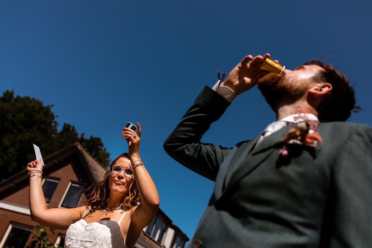 Bruidspaar proost terwijl bruidegom een shotje neemt
