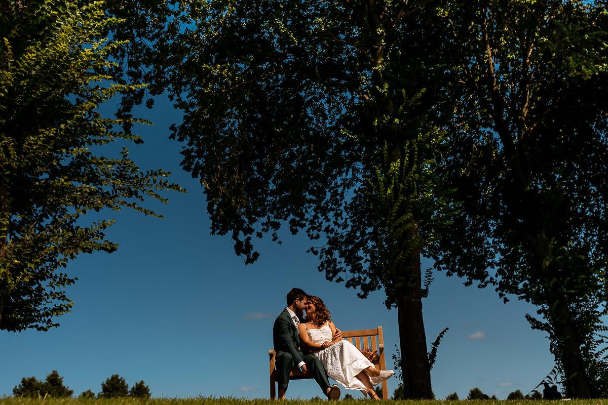 Bruidspaar op bankje in de zon