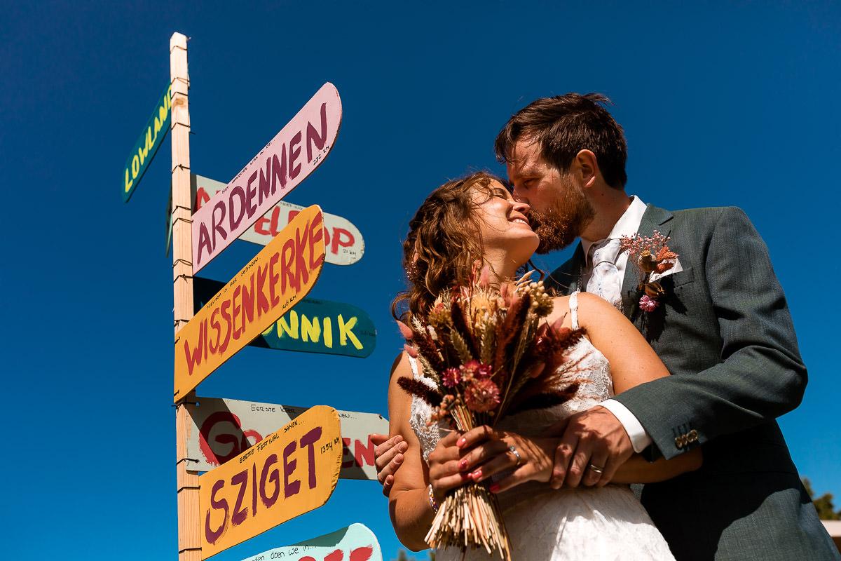 Bruidspaar kust elkaar voor wegwijsborden