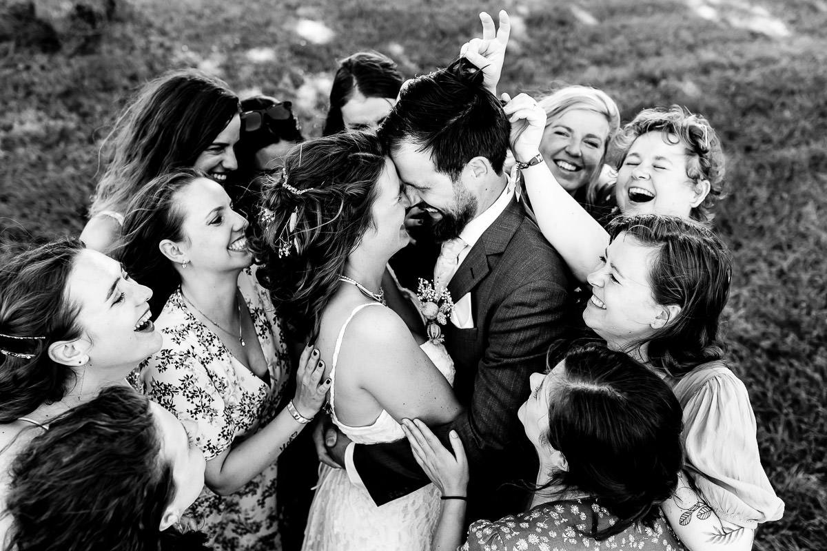 Bruidspaar wordt omringd door vrienden met een groepsknuffel