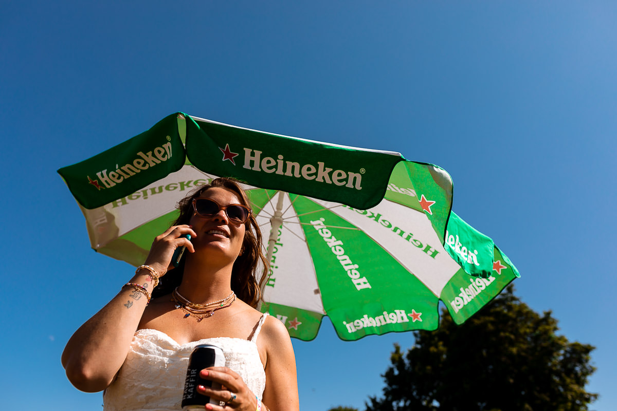 Bruid aan de telefoon voor een heineken parasol