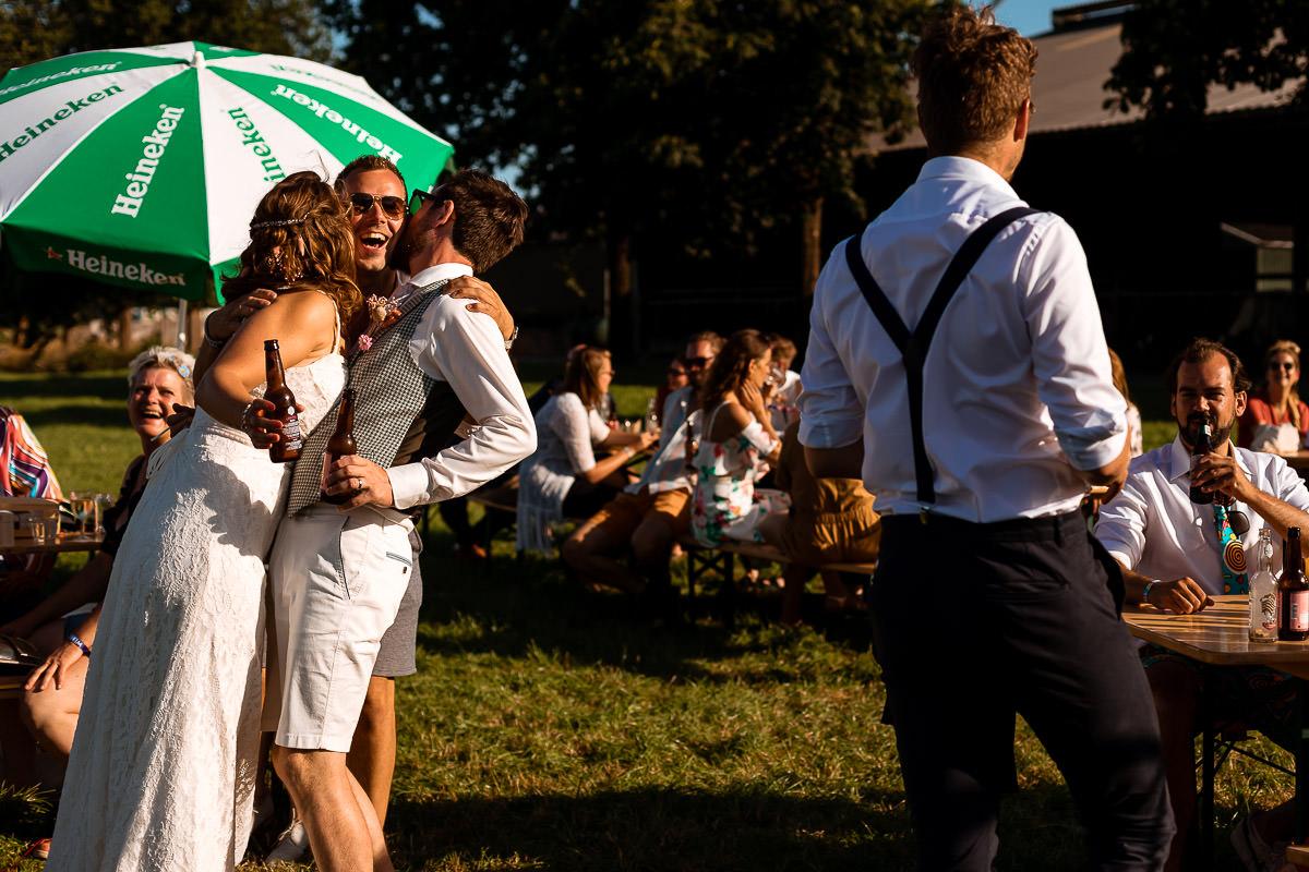 Bruidspaar omhelst vriend intens