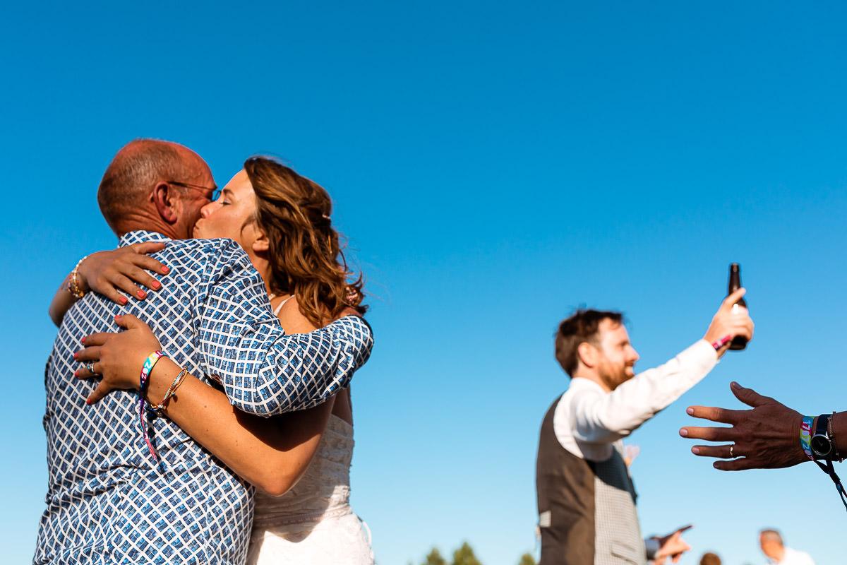 Bruid omhelst en kust vader terwijl bruidegom op de achtergrond proost
