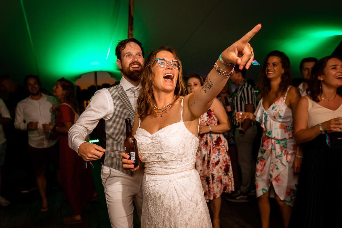 Bruid wijst naar vrienden met biertje in d'r hand