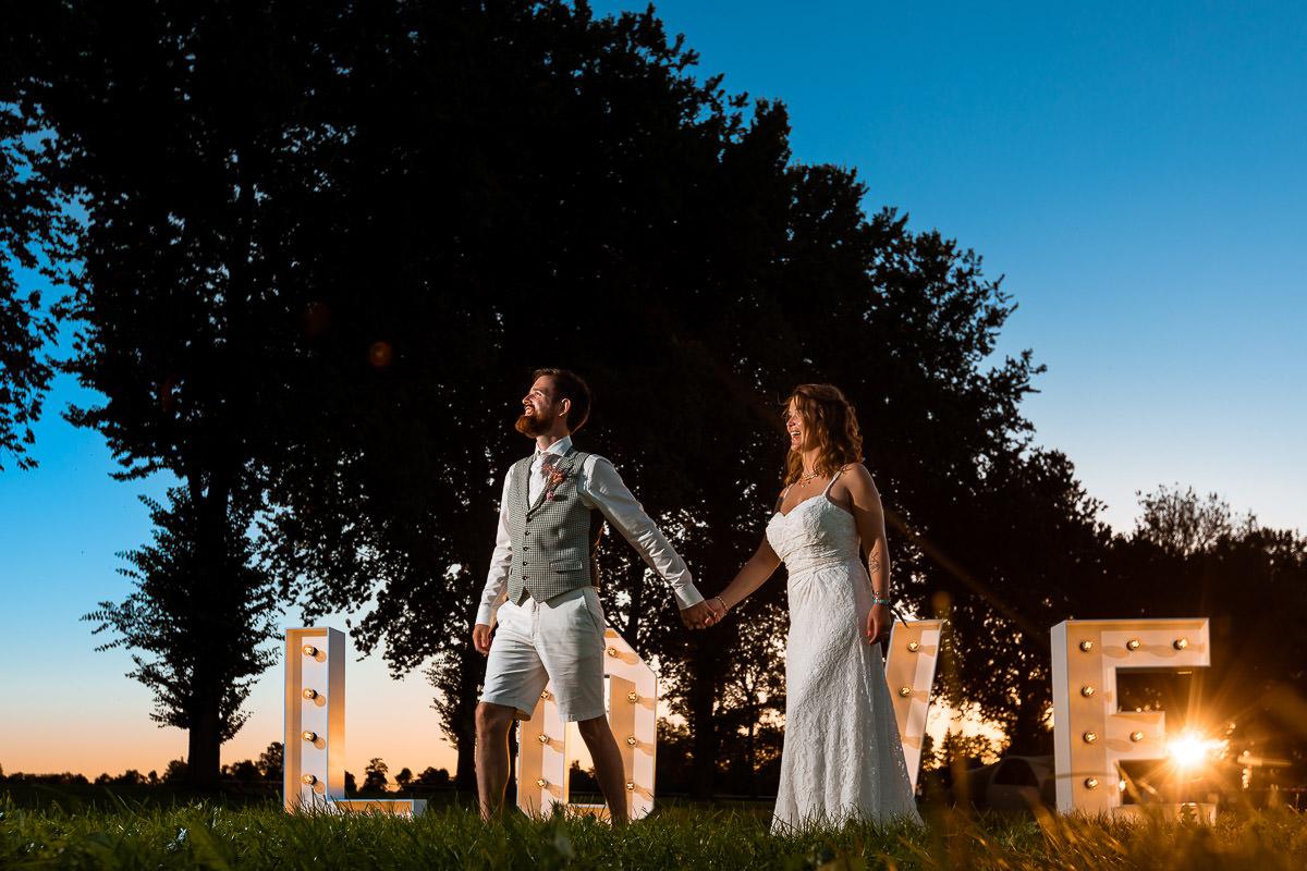 Bruidspaar poseert voor loveletters tijdens zonsondergang